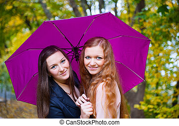 Two girls under umbrella in autumn park