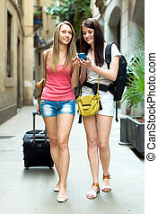 Two girls using  GPS navigator for find a way