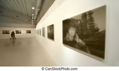 Two girls walk at photography exhibition in empty room