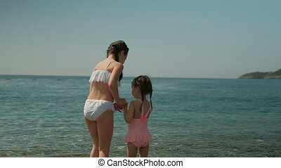 Two girls walk on water by sea on summer day outdoors.