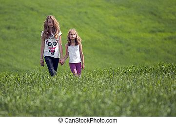 Two girls walking on a green field