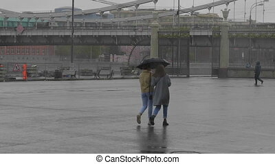 Two girls walking under one umbrella in a park along the...