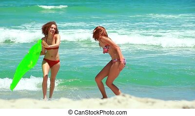 Two girls walking up from the water at the beach