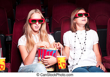 two girls watching a movie at the cinema