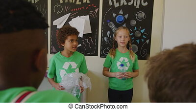 Two girls wearing recycle symbol tshirt holding plastic ...