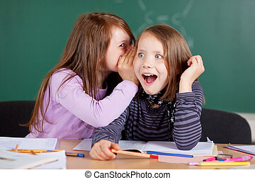 Two girls whispering in class