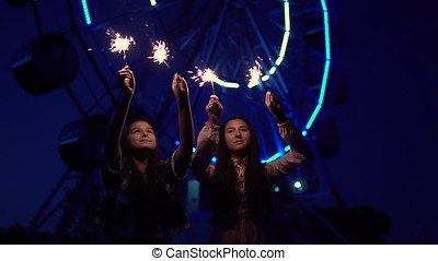 Two girls with fireworks in their hands on the background of a Ferris wheel. slow motion. HD