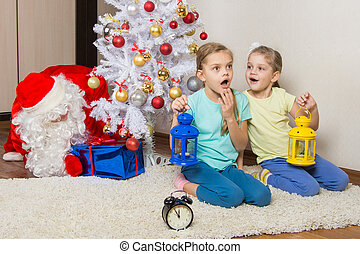 Two girls with flashlights dreaming of gifts on New Years...