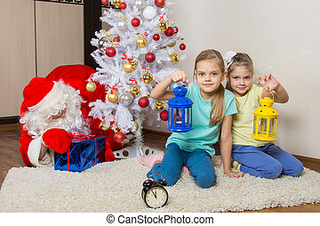 Two girls with flashlights waiting for Santa Claus at the...