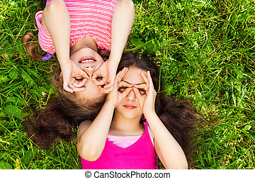 Two girls with hands round shape on face