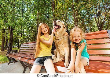 Two girls with happy dog
