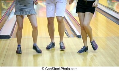 Two girls with one guy dance in bowling club, only legs are...