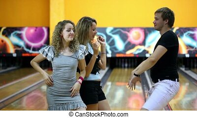 Two girls with one guy dance together at bowling club