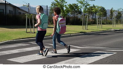 Two girls with school bags crossing the road - Caucasian and...