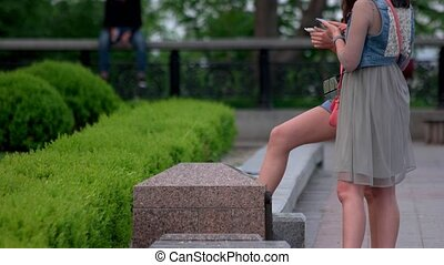 Two girls with smartphones in the park.