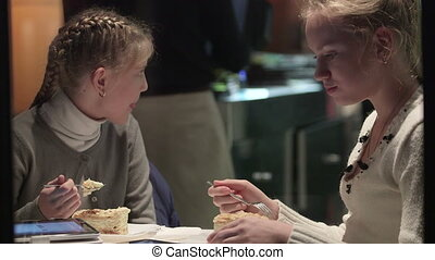 Two girls with tablet computer eating dessert at cafe view through the night window