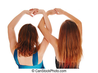 Two girls with there hands up.