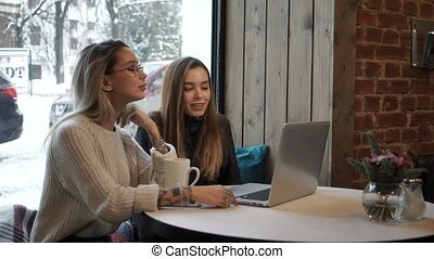Two girls working at a laptop in a cafe