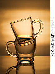Two glass cups on an orange background.