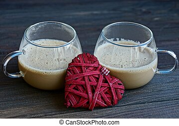 two glass cups with coffee and a red heart on the table