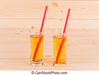 Two glass full of apple juice.