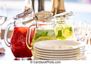 two glass jars of home made fresh raspberry lemonade or virgin mojito cocktail with a straw on the table among dishes prepared for serving