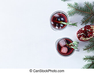 Two glass of pomegranate Christmas cocktail with champagne, soda and rosemary on a white table. Xmas drink.