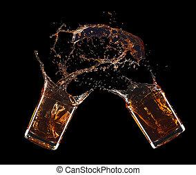 Two glass of whiskey splashing isolated on black background