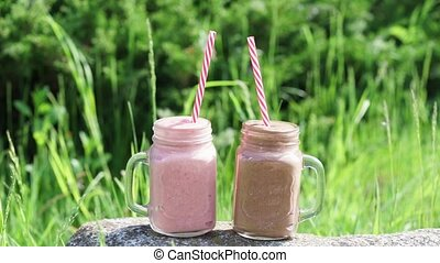 two glass smoothies mugs stand on a rock on a Sunny day