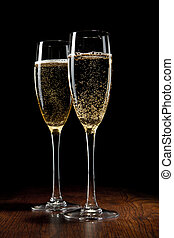 two glass with a champagne on a wooden table