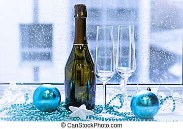 Two glasses, a bottle of champagne and Christmas-tree decorations