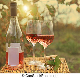 Two glasses and bottle of the rose wine in autumn vineyard....