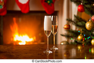 Two glasses being filled with champagne on table next to Christmas tree