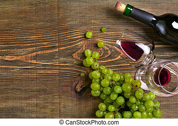 Two glasses, bottle of red wine and grape on a wooden table. Top view. Copy space. Flat lay. Still life