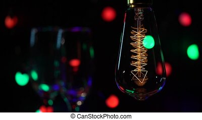 Two glasses champagne are lit against the background of retro light bulbs flashy multicolored flashlights background. Close up