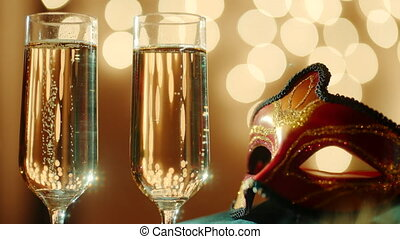 Two glasses filled with bubbly champagne and carnival...