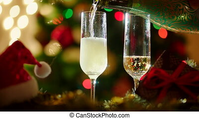 Two glasses filling with champagne on christmas night