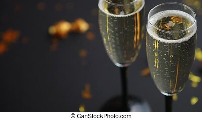 Two glasses full of sparkling champagne wine with golden...