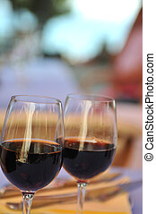 two glasses in outside restaurant with black wine