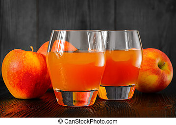 Two glasses of Apple juice and apples on wooden table. Selective focus