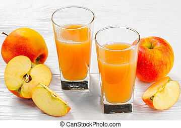 Two glasses of apple juice with Apple slices on a white wood tray