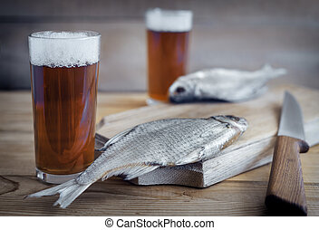On a wooden table two glasses of beer, next to the cutting Board dried fish and a knife.