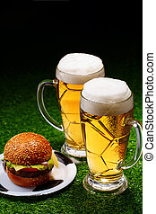 Two glasses of beer and hamburger on green grass.