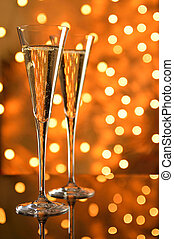Two glasses of champagne against bokeh background.