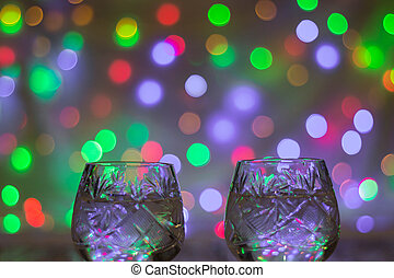two glasses of champagne against bokeh lights background