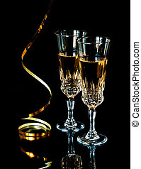 Two glasses of champagne and golden serpentine on a black...