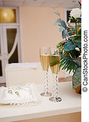 two glasses of champagne and pillow with rings on the table for wedding ceremony