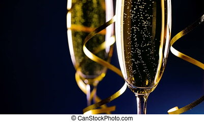 Two glasses of champagne and ribbons on dark blue background...