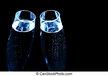 Two glasses of champagne on black stylish background.