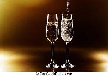 Two glasses of champagne on golden background.